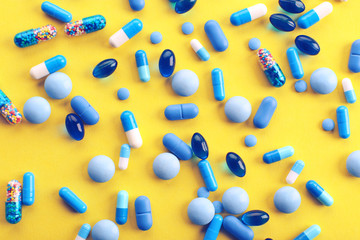 Heap of pills on yellow background