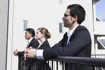 屋上からオフィス街を眺めるビジネスパーソン