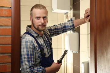 Portrait of handsome plumber in bathroom