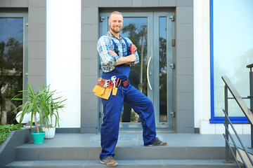 Handsome plumber with pipe wrench  standing on doorstep