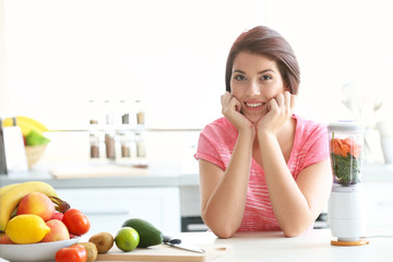 Young beautiful woman making juice with fruits and vegetables in the kitchen