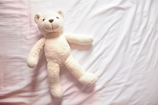 Smiley White Bear Doll Laying On Bed