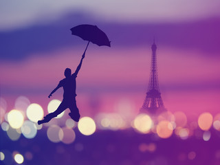 Abstract background. silhouette of a man holding umbrella flying over night Paris , France with eiffel tower on a background. Vintage style colored picture