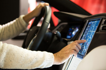 HELSINKI, FINLAND - NOVEMBER 04, 2016: The interior of a Tesla Model X electric car with large touch screen dashboard.  Man using gps navigation system.