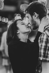 Black-and-white photo of a happy couple embracing  kissing in the evening on  light garlands