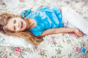 little cute girl in blue shirt lying on the bed