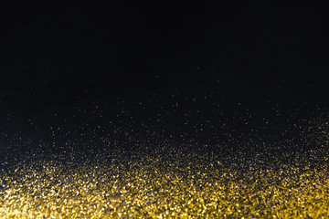 Golden glitter sand texture border on black, abstract background.