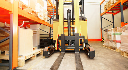 Forklift, shelves and racks with pallets in distribution warehou