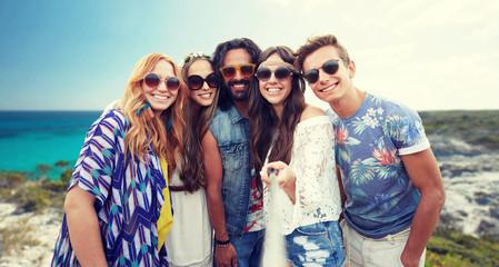 happy hippie friends with selfie stick on beach