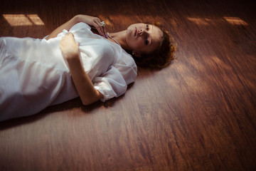 beautiful young woman in white nightie lying on the floor