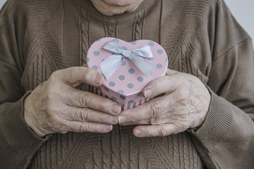 wrinkled hands holding a heart shaped gift