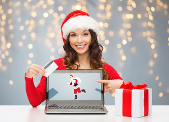 woman in santa hat with laptop and credit card