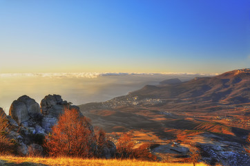 view from the top of the mountains to the city in the valley. Beautiful early morning, gentle light, clouds and fog in the distance over the sea. Amazing scenery.