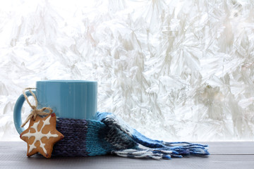 drinks for the winter season/ blue mug with a warm scarf and homemade cakes on the background of frozen window