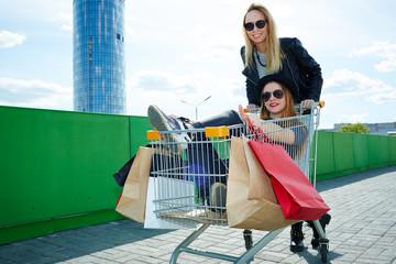 Girls posing in shopping trolley
