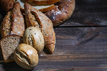 variety of bread on wooden table.