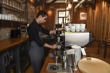 young italian barista or coffee maker at restaurant shop preparing milk cream at cafe machine