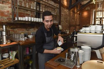 young italian barista or coffee maker at restaurant shop preparing milk cream at cafe machine