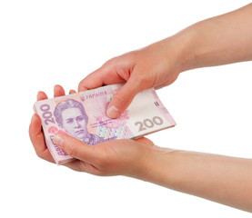Stack of money 200 Ukrainian hryvnia in female hands isolated.