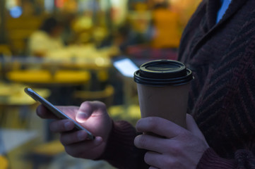 hands using a phone texting on smartphone app and holding paper coffee cup