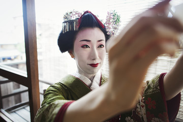 A woman dressed in the traditional geisha style, wearing a kimono and obi, with an elaborate hairstyle and floral hair clips, with white face makeup with bright red lips and dark eyes taking a selfie of herself.
