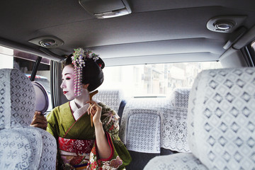 A woman dressed in the traditional geisha style, wearing a kimono with an elaborate hairstyle and floral hair clips, with white face makeup with bright red lips and dark eyes in a car using a hand mirror.
