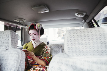 A woman dressed in the traditional geisha style, wearing a kimono with an elaborate hairstyle and floral hair clips, with white face makeup with bright red lips and dark eyes in a car using a smart phone