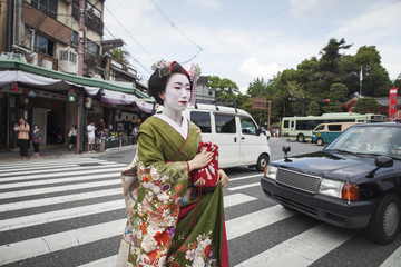 A woman dressed in the traditional geisha style, wearing a kimono and obi, with an elaborate hairstyle and floral hair clips, with white face makeup with bright red lips and dark eyes crossing a street.