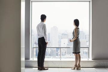A businessman and businesswoman standing by a large window overlooking a city.