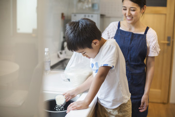 Family home. A mother and son standing at a sink.