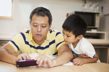 Man and his son looking at screen of smart phone