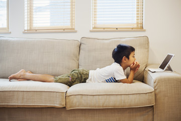 Family home. A boy lying on a sofa watching a digital tablet.