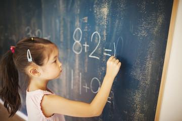 Girl writing in chalk on blackboard in school