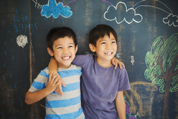 Two boys standing with their arms around by blackboard