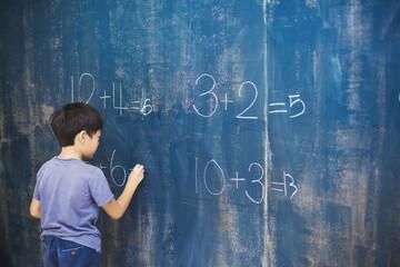 Boy writing in chalk on blackboard