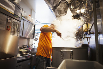 The ramen noodle shop kitchen. A vast pot on the stove, and steam rising.  A man cooking noodles..