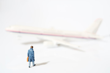 Toy businessman / View of miniature toy, businessman walking and airplane on white background.