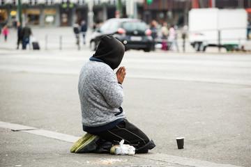 a beggar on the street, praying man