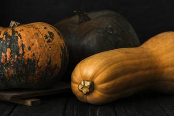 raw big yellow long pumpkin with orange round orange one and brown one