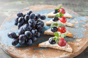 cheese and grapes sandwiches on an impressive board, selective focus