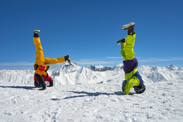 Two snowboarders are on hand upside down in high mountains