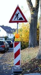 Schild Baustelle mit rotweißer Barke und Warnlicht