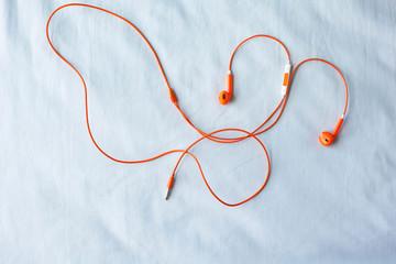 Orange color earphone on fabric background.