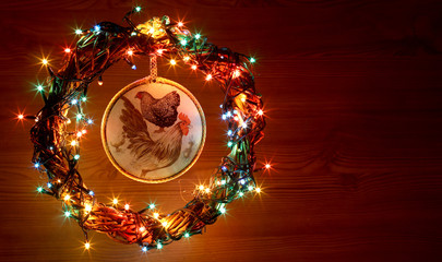 Happy New Year 2017 on the Chinese calendar of rooster template copyspace card with hand made craft roosters decoupage in decorated Christmas wreath and garlands of colored light. Wooden background.