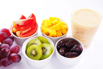Close up of healthy glass of mixed fruits smoothie with fruits on white background.