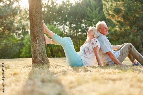 senioren paar sitzt r cken an r cken im gras stockfotos. Black Bedroom Furniture Sets. Home Design Ideas