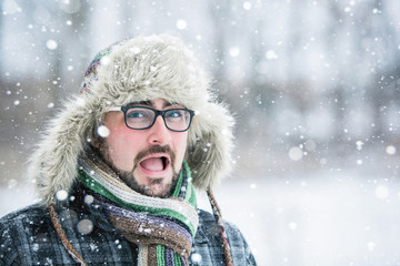 open-mouthed, adult man with beard wearing glasses. Winter, snow, a man in a fur hat.