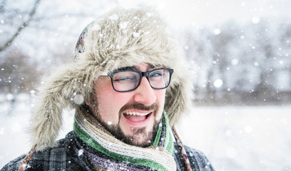 Adult man with beard wearing glasses. The man smiles. Winter, snow, a man in a fur hat. Man winks