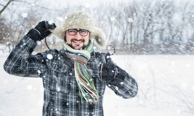 Adult man with beard wearing glasses. The man smiles. Winter, snow, a man in a fur hat. thumbs up