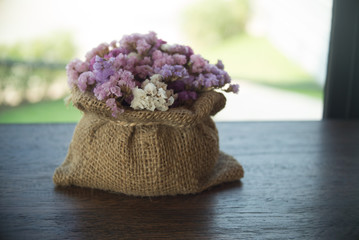 abstract image of bouquet of dried flowers hanging on rope against block background at evening light